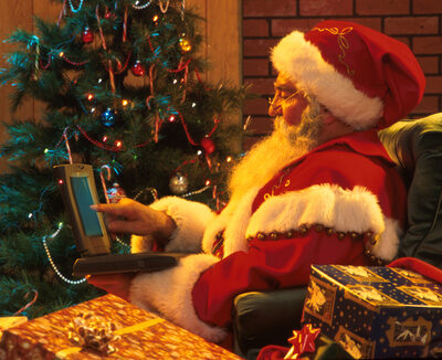 Santa Claus Typing on Laptop Computer W/ Presents & TreeInside Home Christmas